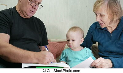 Attractive baby boy draws a pen with his grandparents home...