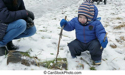 Attractive baby playing with mother in winter on the street. The boy in the hands of the branches of trees
