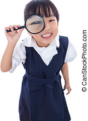 Happy Asian Chinese little primary school girl holding...