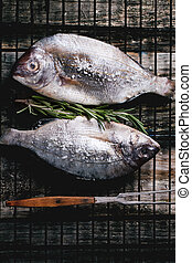 Tow raw dorado fish with rosemary on grill - Top view on tow...