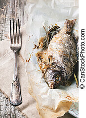 Grilled dorado fish with rosemary served on baking paper....