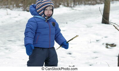 Portrait of an attractive kid looking at the camera in winter forest. Kid warm sport dressed in a blue jacket and dark pants, about a year