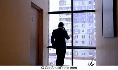 View of man talking on phone outside the room - View of man...