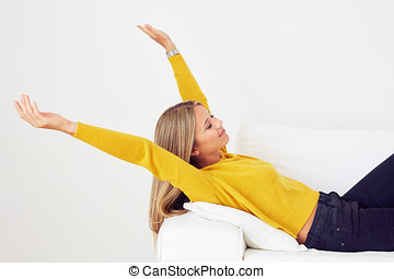 Young woman stretching on a couch in the living room