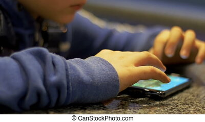 Child Playing with Mobile Phone on the Table. Teenager hands...