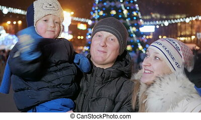 Happy family celebrating new year in the town square. Everyone looks at the camera and smile. Against the background is decorated Christmas tree.