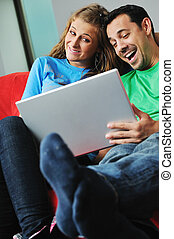 happy couple have fun and work on laptop at home on red sofa...