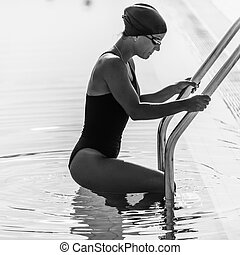 Female swimmer geting in to the pool
