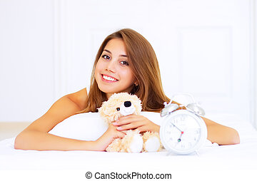 smiling girl lying on the bed with a teddy bear