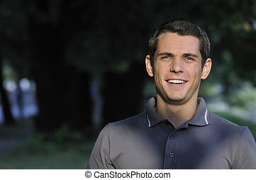 young casual man outdoor portrait smiling - happy young...