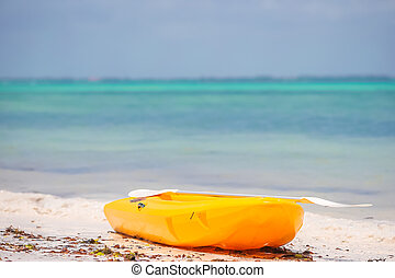 Small boat on the white sandy tropical beach and turquiose...