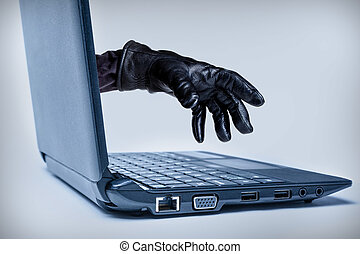Cybercrime Concept - A gloved hand reaching out through a...