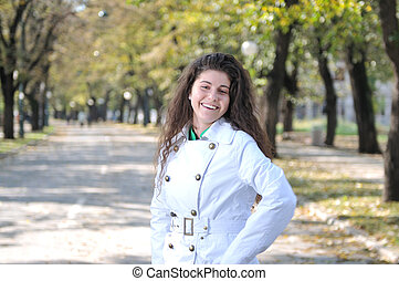 Happy young woman smiling outdoors in park