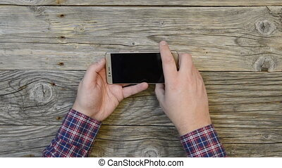 man looks smartphone - A man in a plaid shirt looks...