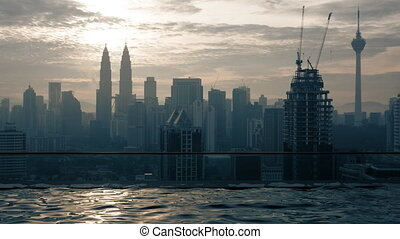 Time lapse view of swimming pool on the skyscraper roof against sunrise building cityscape. Kuala Lumpur, Malaysia