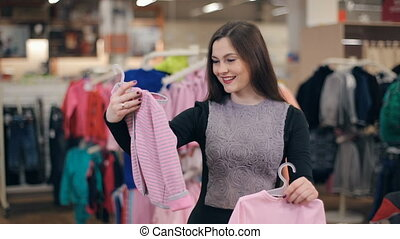 Woman chooses clothing for twins - Young smiling woman...