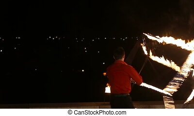Fire show in the night. - Artist turns the big fire cube.Man...