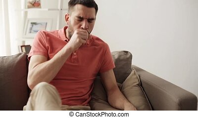 unhappy sick man coughing at home - people, healthcare and...