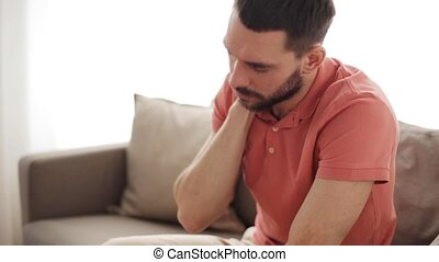 unhappy man suffering from neck pain at home - people,...