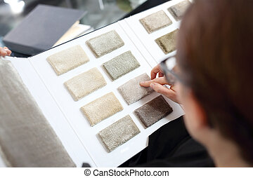 probe carpets - Woman in shop with carpets chooses carpet...