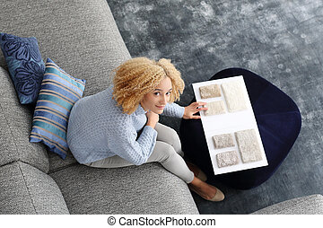 Shopping coverings. - Woman chooses carpet picker sitting on...