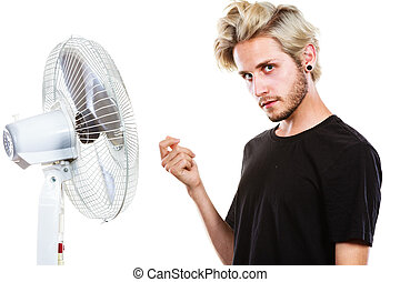 Young man in front of cooling fan - Air conditioning, heat,...