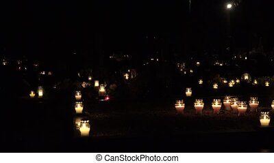 Graveyard decorated with candles for All Saints Day at night. 4K