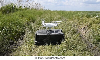 Quadrocopters on a plastic box in the grass. Preparing for...
