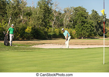 Golfer playing from sand trap, ball visible in the air
