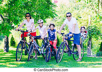 Happy family on bicycles in the park - active family concept