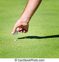 Placing golf ball on the green