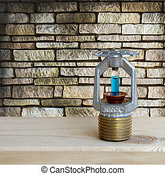 fire sprinkler with fire on wooden and stone wall...