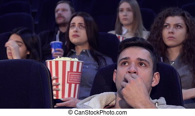 People watch serious film at the movie theater - Young...