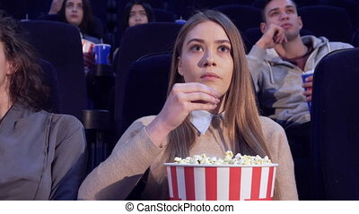 Girl slowly puts the popcorn in her mouth at the movie...