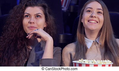 Girls share impressions at the movie theater - Two caucasian...