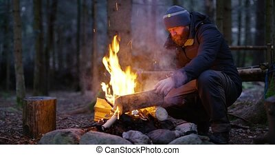Adult man fires up campfire outdoor in the forest - Adult...