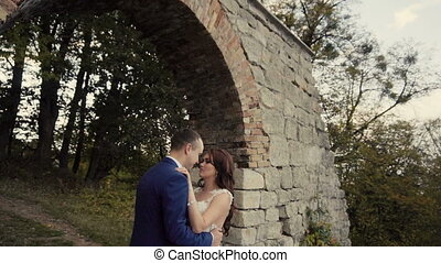 Wedding Couple Embracing Before Old rock Wall - Walking of...
