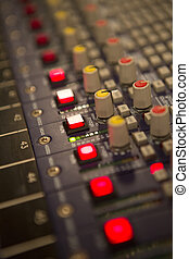 Audio mixer mixing board fader and knobs at night during a...