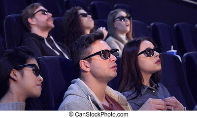 People watch 3D film at the movie theater - Young people...