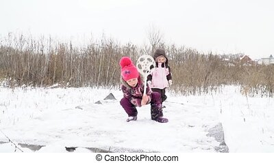 Children beat out mat in winter - Two children girls...