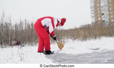 Woman sweeps the snow from carpet - Woman in a red sports...