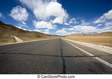 Straight arid desert and mountain road in Tibet - Straight...