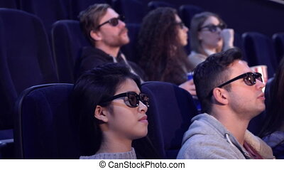 People enjoy 3D effects at the movie theater - Young people...