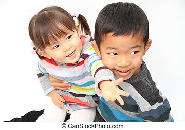 Japanese brother and sister sitting on his knee (7 years old...