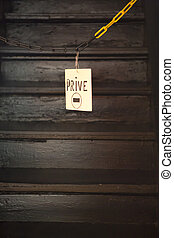 Beat up no tresspassing sign hanging on chain with stairs in...