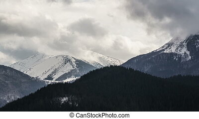 Heavy clouds in snowy mountains time lapse. Fast moving sky...