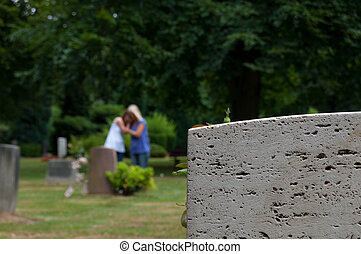 Mourning at the grave - Two women mourn at the grave.