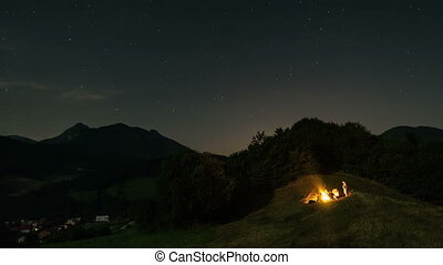 People sitting around campfire at starry moonlight night...