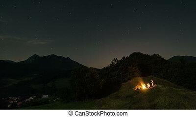 People sitting around campfire at starry moonlight night...