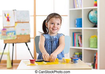 Little kid toddler girl creating toys from playdough -...
